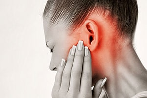 Woman holding ear in pain