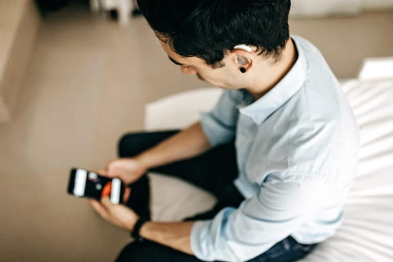 Man on cell phone with one hearing aid in