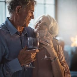 Two older adults enjoying a glass of wine