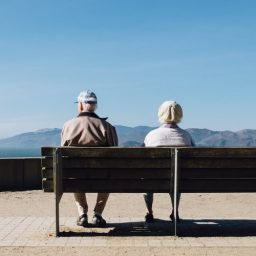 Older couple sitting on a bench.