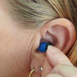 Woman inserting earplug into her ear.